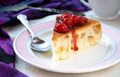 Кусочек шарлотки с вишней на тарелке с ложечкой