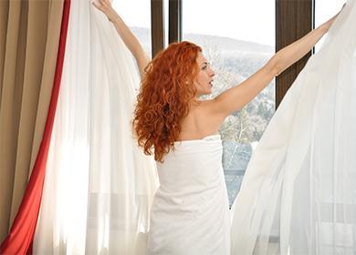 Девушка открывает шторы в комнату