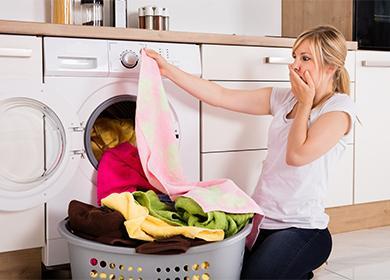 Женщина смотрит на белье возле стиральной машины
