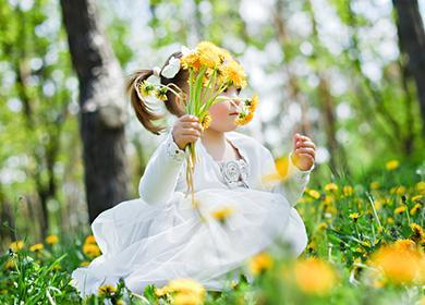 Девочка в белом платье держит букет одуванчиков