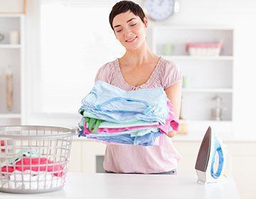 Довольная женщина со стопкой чистой одежды