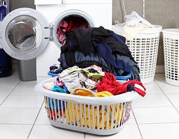 Корзина с бельём перед стиральной машиной