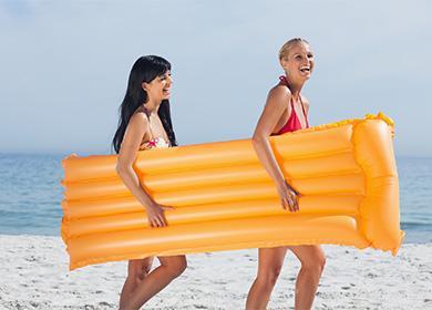 Девушки несут надувной матрас