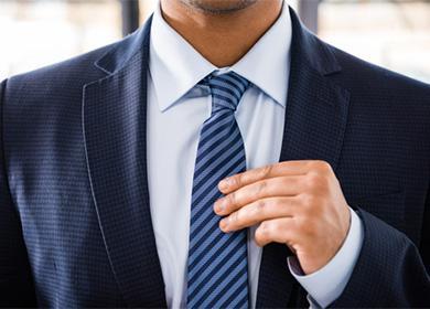 Мужчина держит в руках галстук