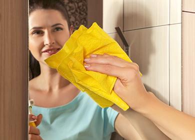 Женщина протирает зеркало жёлтой салфеткой