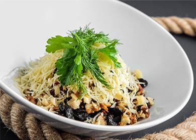 Слоеный салат с курицей, сыром и черносливом в тарелке