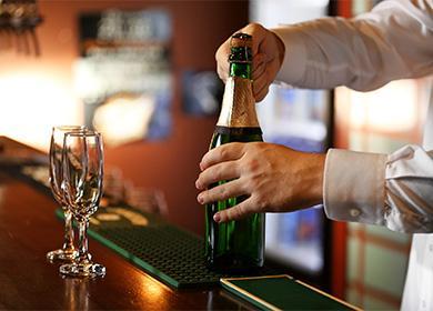 Бармен открывает бутылку шампанского