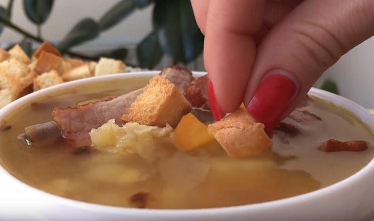 Гороховый суп с копчеными ребрышками принято подавать с гренками.