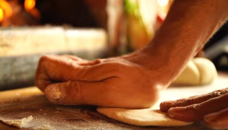 делим тесто на небольшие кусочки и раскатываем их скалкой либо разминаем руками.