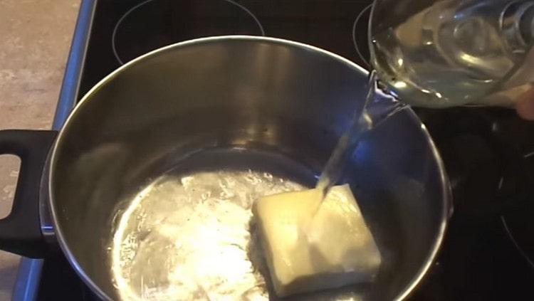 Ставим на огонь кастрюльку, выкладываем в нее сливочное масло и добавляем воду.