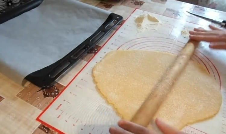 Посыпаем тесто сахаром и слегка проходимся по нему скалкой.