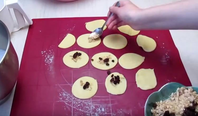 На каждый кружочек кладем немного начинки из орехов и изюма.