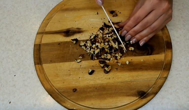Орехи измельчаем, перемешиваем с промытым изюмом.
