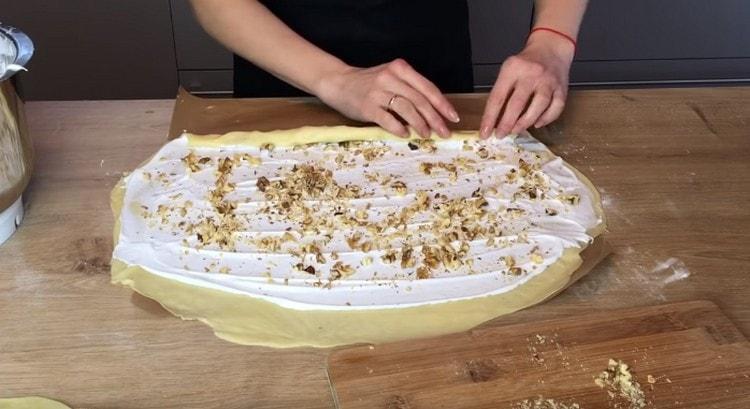 Посыпаем белковый слой орехами, а затем сворачиваем тесто в рулет.
