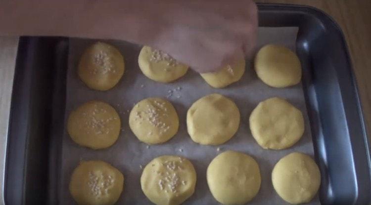 Посыпаем печенье кунжутом.
