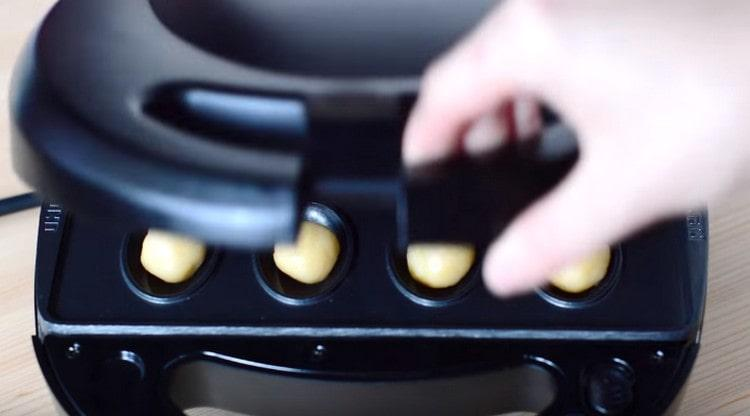 Выкладываем шарики в форму, закрываем и выпекаем до золотистого цвета.