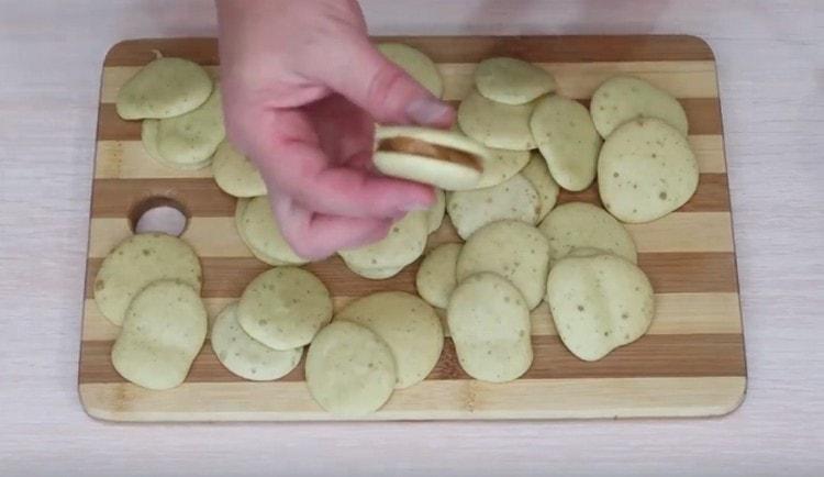 Берем по два печенья, смазываем их вареной сгущенкой и соединяем.