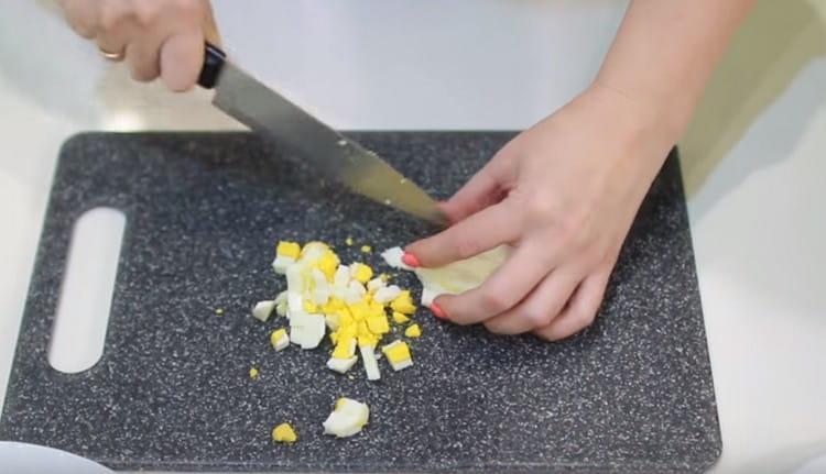 Нарезаем кубиком отварные яйца.