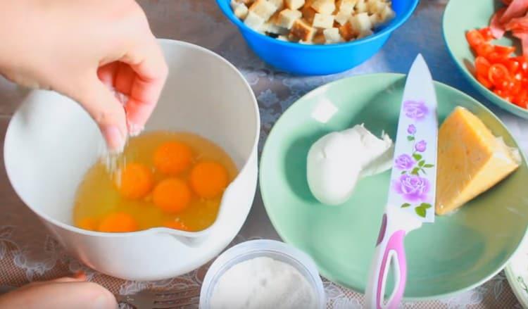 В миску выбиваем яйца и добавляем немного соли.