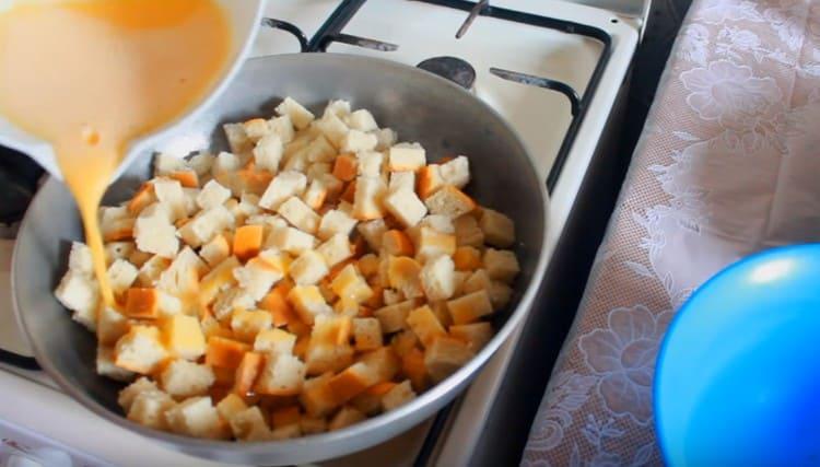 На сковороду выкладываем кусочки батона и равномерно заливаем их яичной массой.