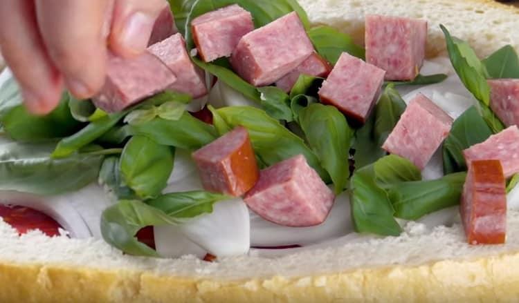 Выкладываем слой из нарезанных кусочками копченых колбасок.