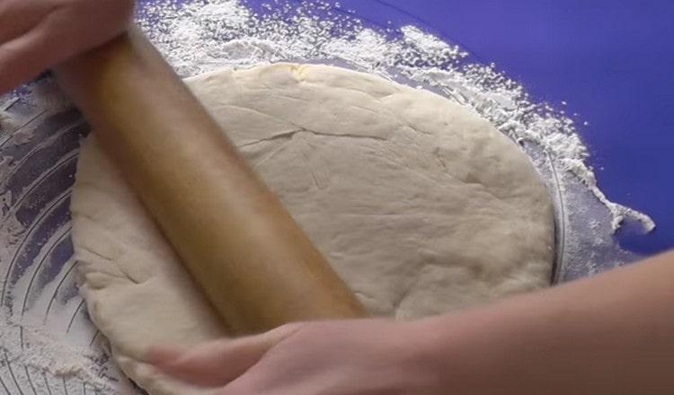 На присыпанной мукой поверхности раскатываем тесто.