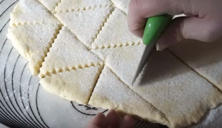 Фигурным ножом нарезаем тесто на треугольнички.