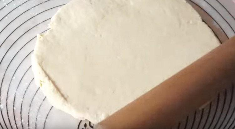 Раскатываем тесто скалкой.
