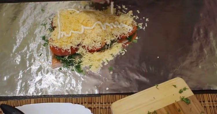 Слегка сбрызгиваем рыбу под сыром растительным маслом и делаем на нем сеточку из майонеза.