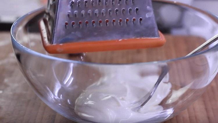 Добавляем к майонезу немного натертого на терке чеснока.