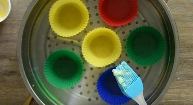 Смазываем растопленным сливочным маслом силиконовые формочки.