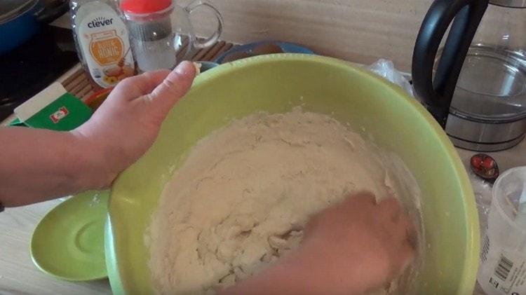 Сначала замешиваем тесто ложкой, а потом уже месим руками.