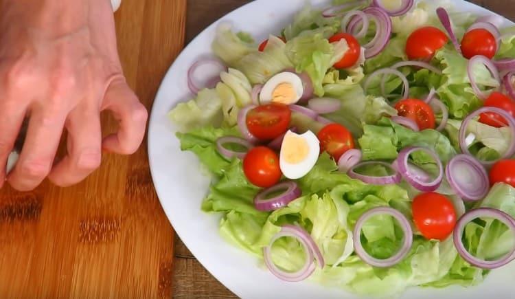 Добавляем в салат отваренные вкрутую и нарезанные пополам перепелиные яйца.