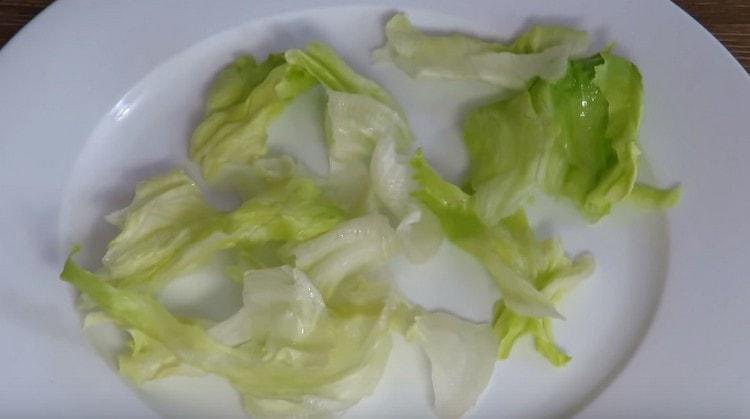 На большое сервировочное блюдо выкладываем салат айсберг.