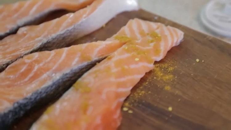 Для приготовления лосося в духовке в фольге посолите поперчите рыбу