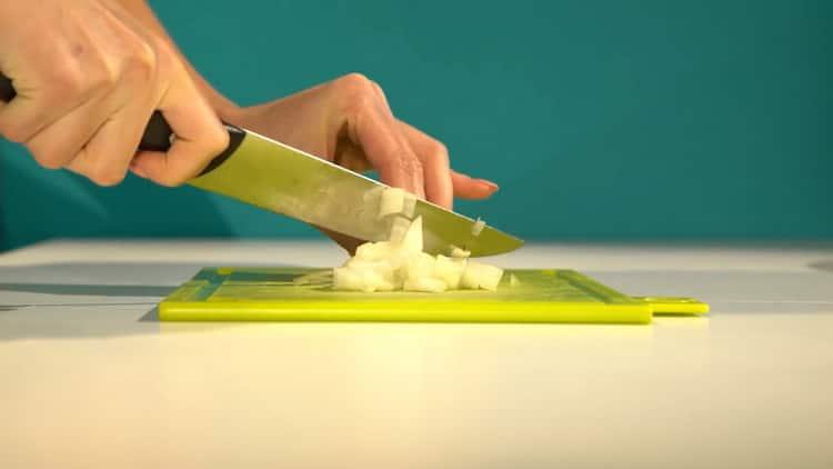 Для приготовления палтуса в духовке, нарежьте лук