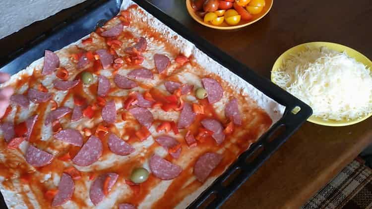 Для приготовления пиццы из лаваша в духовке нарежьте колбасу