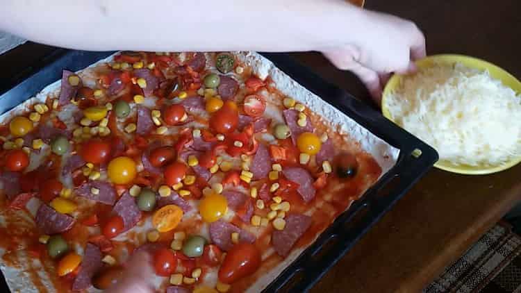 Для приготовления пиццы из лаваша в духовке натрите сыр