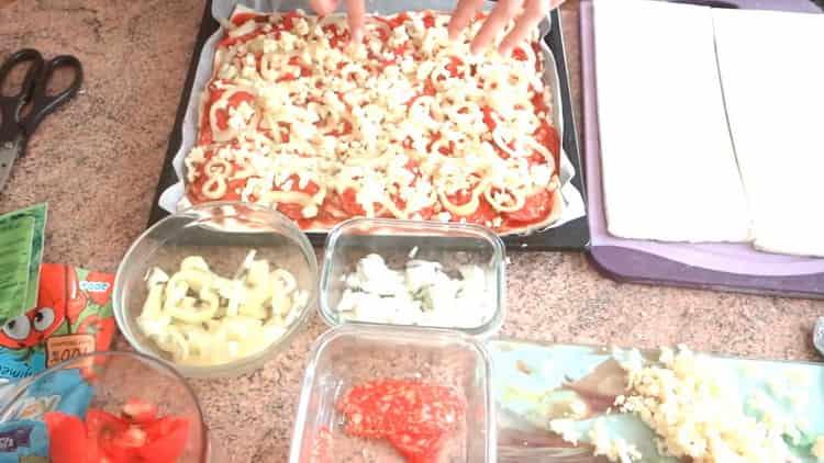 Для приготовления пиццы из слоеного теста в духовке затрите сыром