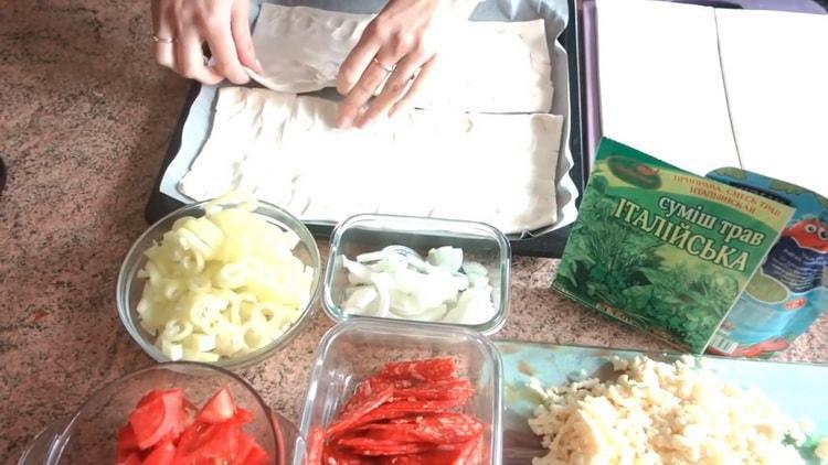 Для приготовления пиццы из слоеного теста в духовке выложите тесто на противень