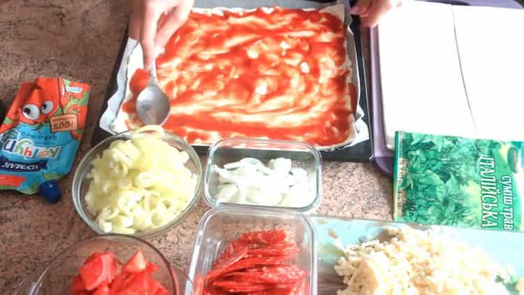 Для приготовления пиццы из слоеного теста в духовке смажьте тесто томатом