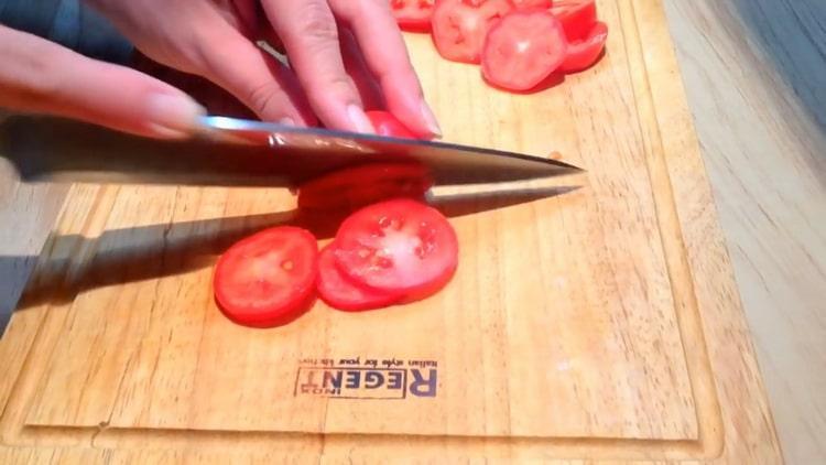 Для приготовления стейков из горбуши, нарежьте помидоры