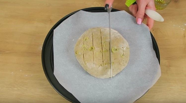 Сформировав круглый хлеб, выкладываем его на застеленный пергаментом противень и делаем на буханке неглубокие надрезы ножом.