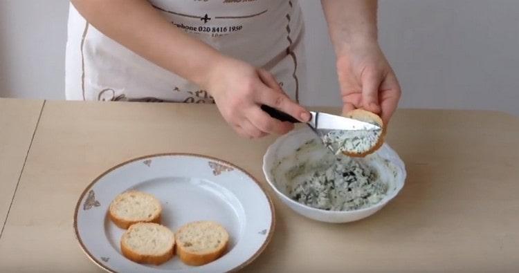 Смесью сыра и зелени намазываем ломтики багета.