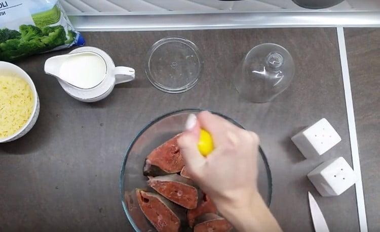 Поливаем рыбу соком половины лимона.