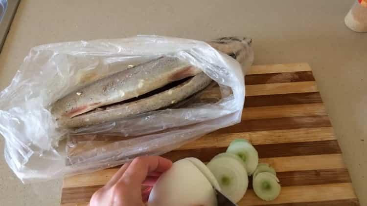 Для приготовления скумбрии в фольге в духовке нарежьте лук