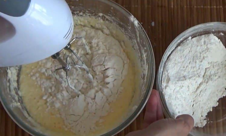 Частями добавляем муку и взбиваем тесто.