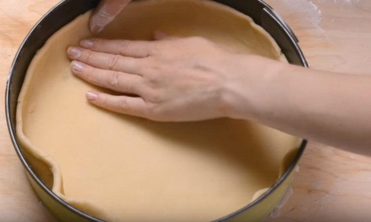 Переносим тесто в застеленную пергаментом форму и делаем бортики.