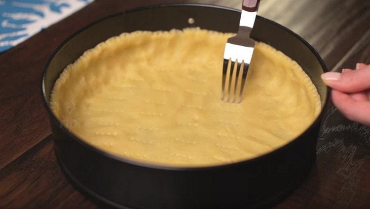 Вилкой накалываем тесто по дну и по бортикам.