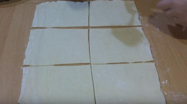 Слоеное тесто раскатываем и разразаем на квадраты.
